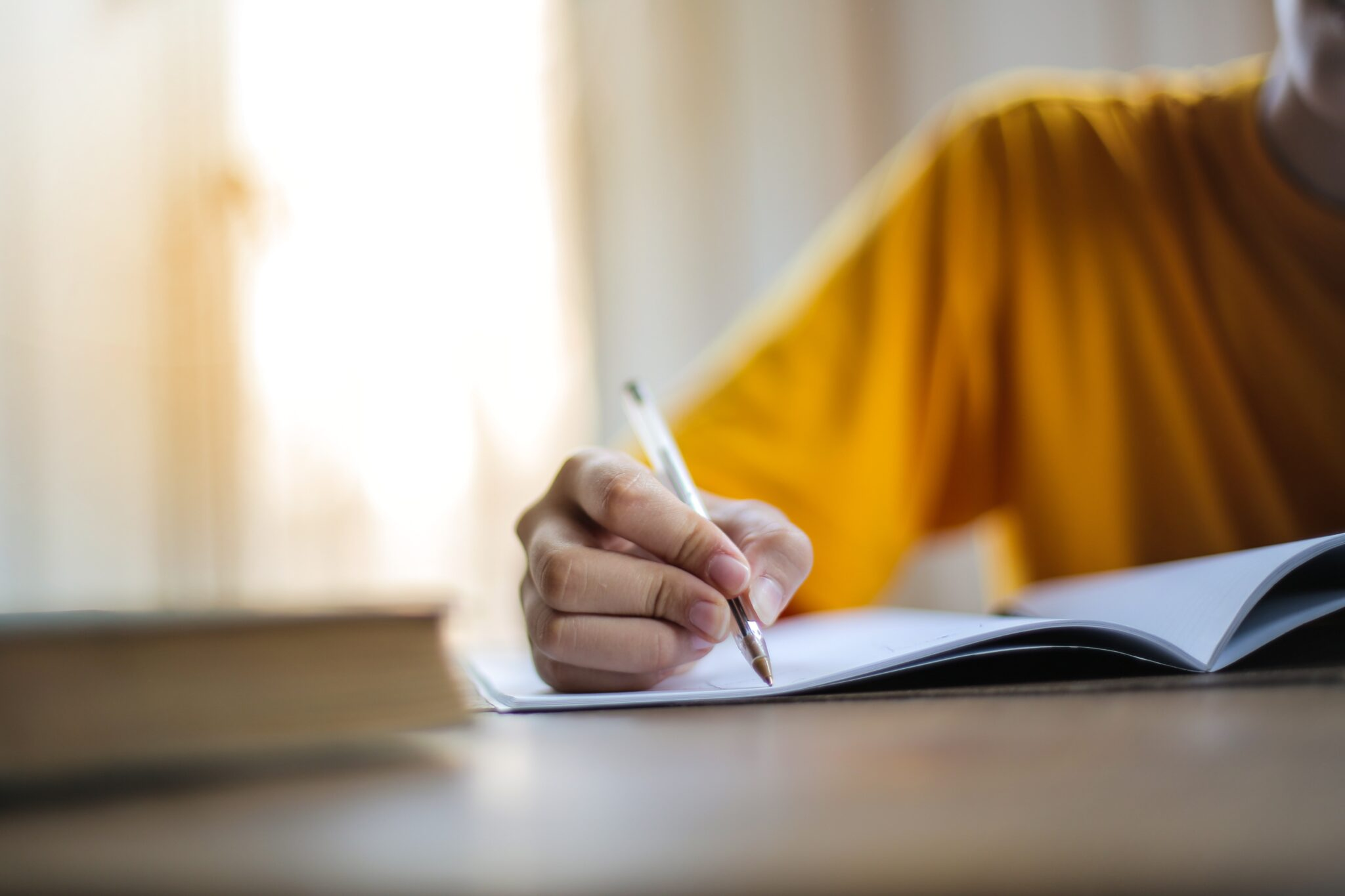 Transcreators are often copywriters experienced in marketing. Description: a person in a yellow shirt writing with a pen in a notebook, which is on a desk.