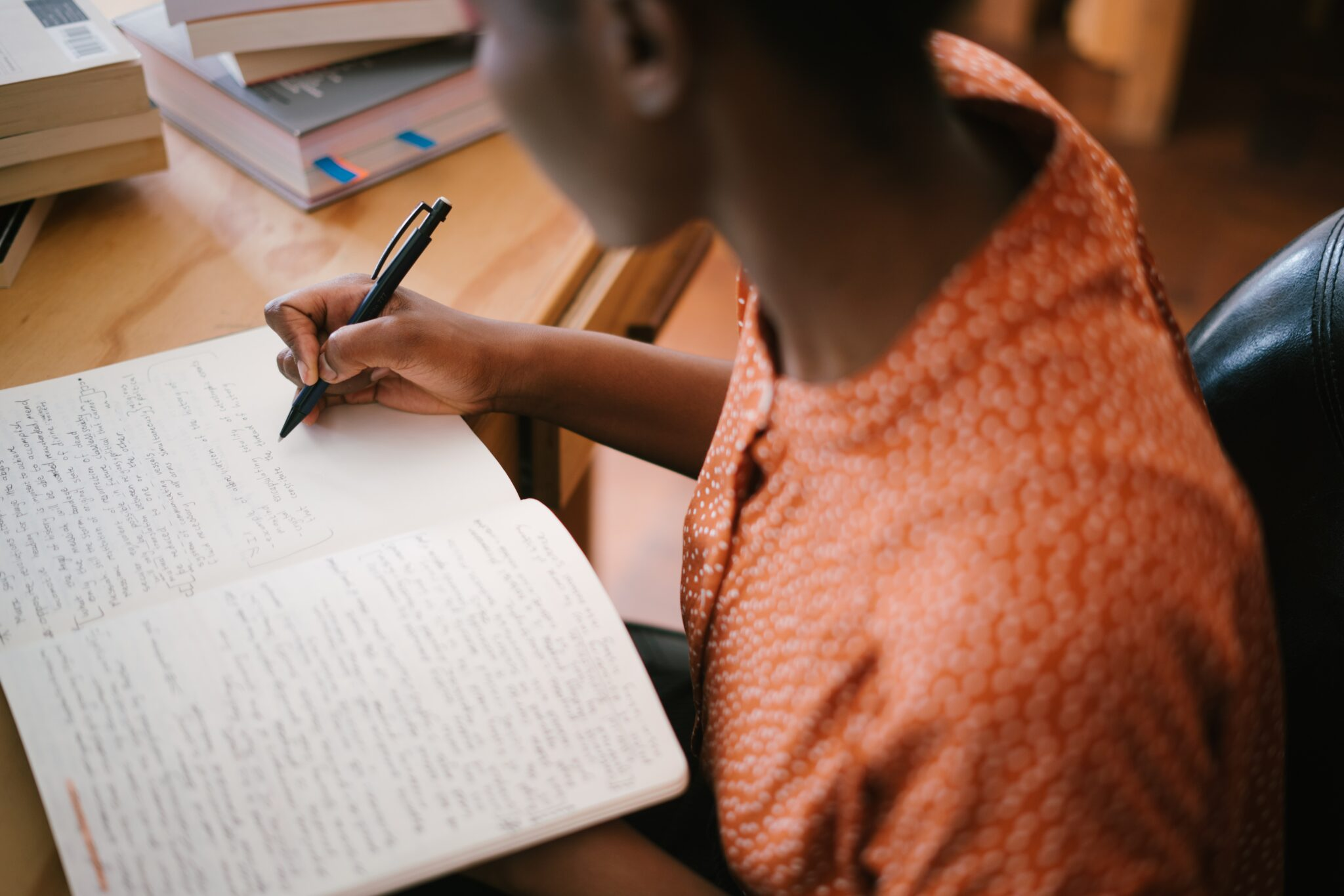 Transliteration takes characters from one alphabet and renders them into another.  Description: A woman wearing an orange blouse is writing in a notebook on her desk, surrounded by books.